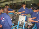 Boys repairing a vehicle engine